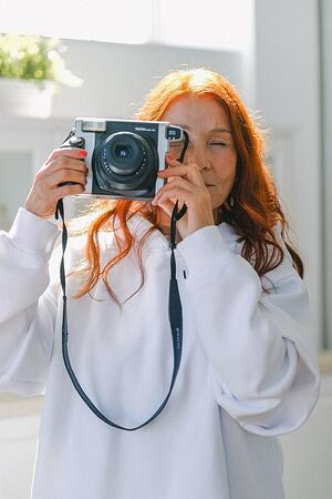 older woman taking picture with a camera