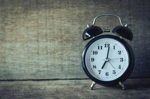 analog alarm clock over wooden background