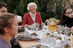 grandmother eating outdoors with family