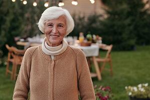 older woman standing in front of lighting hung in her backyard