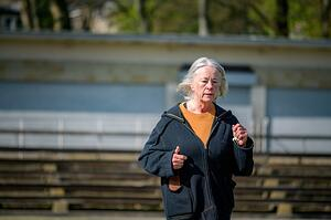 older woman running outside in a park exercising