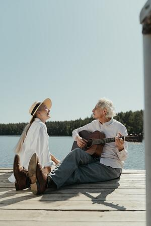 older couple playing music together on dock over lake outside