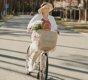 older woman biking with basket full of goods