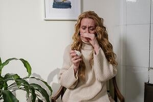 woman suffering from allergies indoors