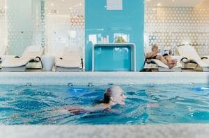 older woman swimming laps in pool