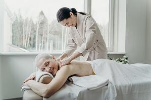 older woman receiving shoulder massage