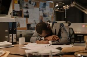 older man taking a nap at his desk