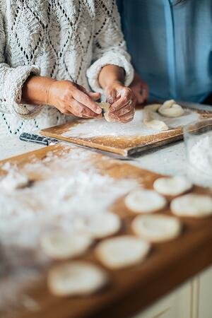 grandmother and daughter baking cookies together in kitchen