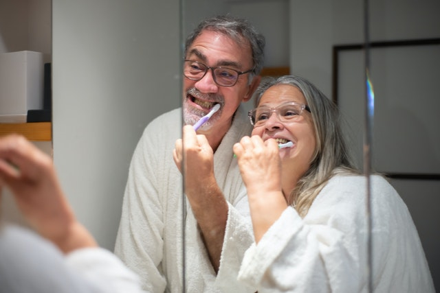 older couple brushing teeth together in the mirror