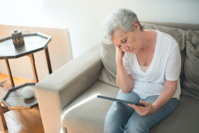 sad woman sitting on couch looking at photo