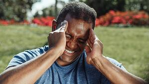 older man suffering from migraine outdoors