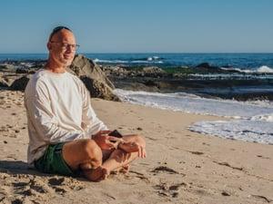 older man taking a break at the beach meditating