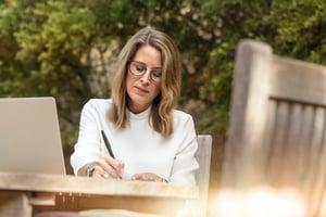 woman writing outside on picnic table