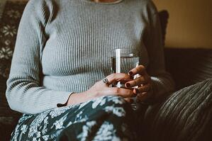 woman at home drinking glass of water