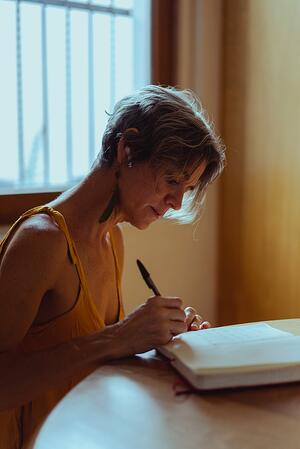 older woman writing in notebook at kitchen table