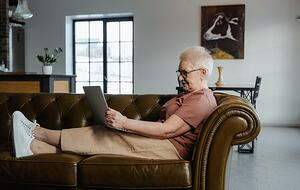 older woman on couch with laptop, social media