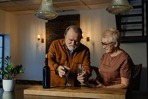 older couple in empty house pouring glass of wine