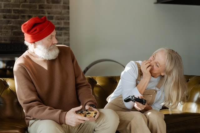 Older couple playing games together inside home