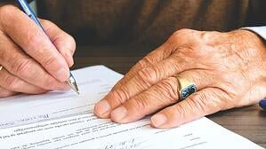 older man signing contract