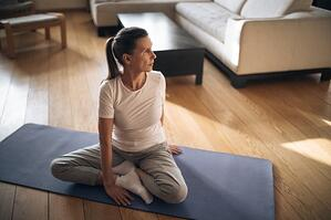 older woman practicing yoga on mat at home
