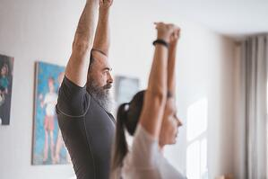 Older man and woman stretching in living room together