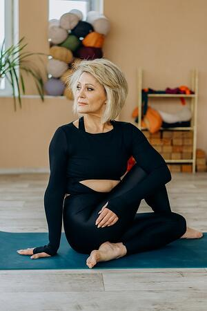 older woman stretching on the floor improving flexibility