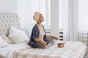 Woman meditating on her bed in the morning