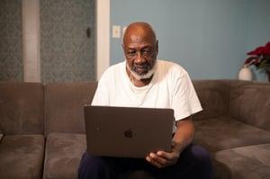 older man sitting down looking at computer screen