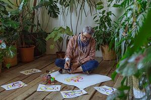 older woman sitting on the floor painting
