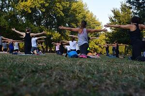 group of women practicing Pilates outdoors in a grassy park