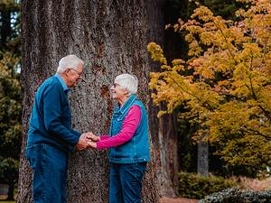 Happy retired older couple holding hands outside in the park
