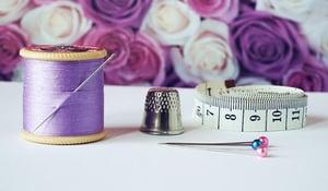 sewing needle thimble tape measure spool of yarn
