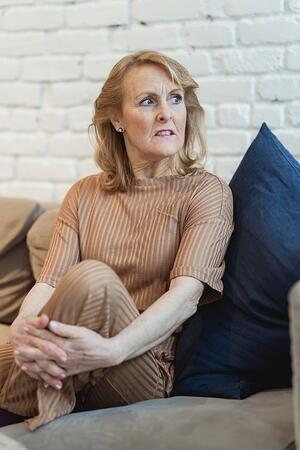 Older woman sitting nervously ono couch_anxiety