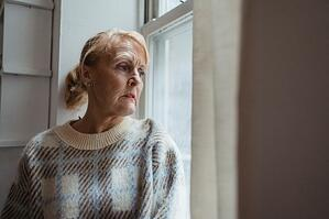 older woman with depression looking outside of window