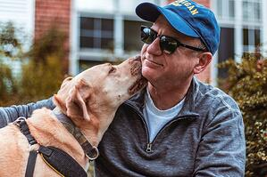 older man receiving attention from therapy dog outside
