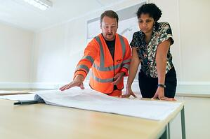 Woman discussing plans with profesional contractor for home renovation