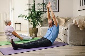 older couple practicing calisthenics at home in living room