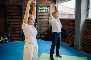 older man and woman stretching in studio gym