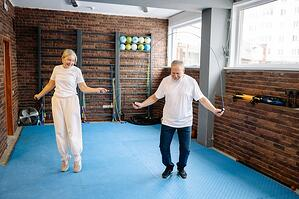 senior couple exercising together jumping rope in indoor studio gym