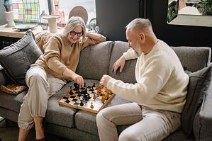 older couple playing chess together on the couch