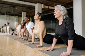senior woman participating in group exercise yoga class stretching