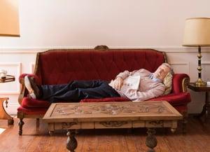 Man sleeping on sofa in well-lit room
