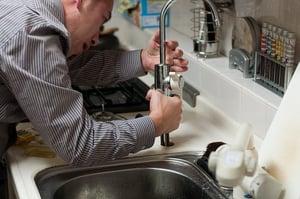 man inspecting kitchen sink