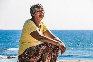 senior woman spending time alone at the beach