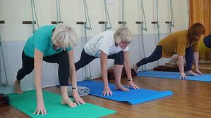 three older women practicing yoga stretching at an indoor studio
