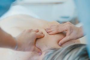 older woman receiving massage on upper back