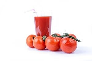four tomatoes in front of glass of fresh tomato juice