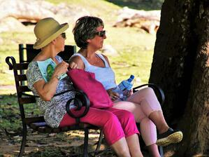 two older women sitting outside in the shade